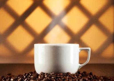 Werbefotografie weisse Kaffeetasse auf Kaffeebohnen